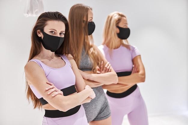 Les athlètes féminines se tiennent la main croisée dans un masque facial. entraînement de remise en forme intense dans une salle de sport industrielle loft.