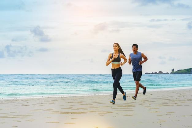 Athlètes de jogging coureur de couple à la plage avec ciel nuageux