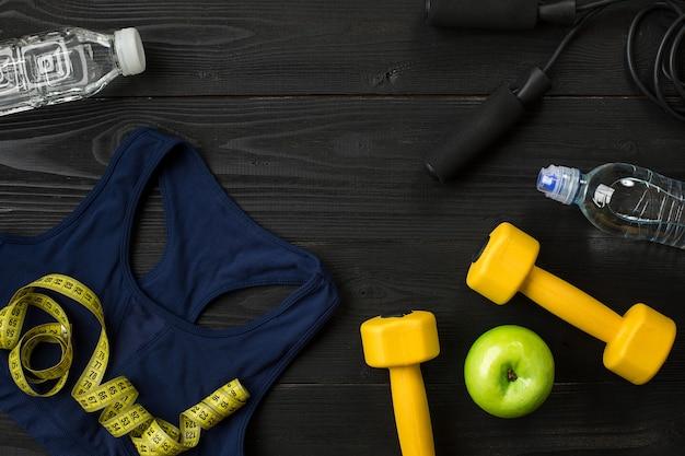 Athlètes avec vêtements féminins et bouteille d'eau sur fond sombre