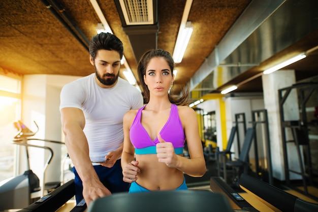 Athlétique belle fille active exerçant sur le tapis roulant avec un entraîneur personnel dans la salle de gym.