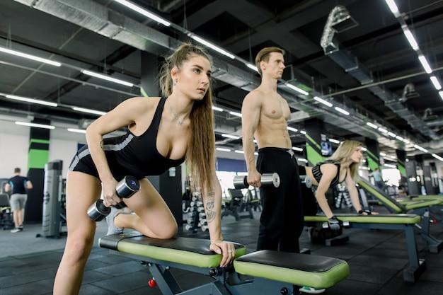 Athlétique deux filles aux cheveux longs vêtus d'un vêtement de sport font de l'exercice sur le banc avec des haltères pour les triceps dans la salle de sport moderne avec leur canapé