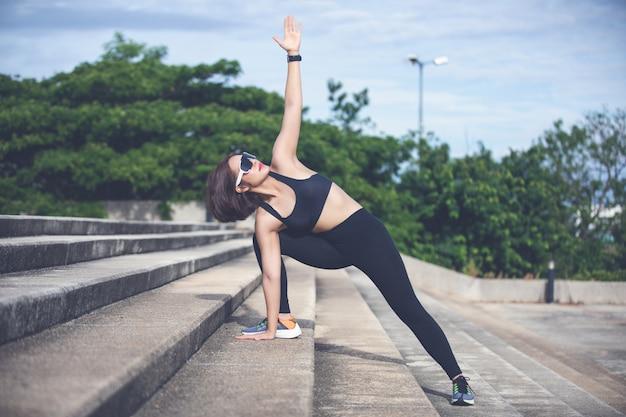 Athlétique femme asiatique échauffement et jeune athlète féminine assis sur un exercice et d'étirement dans un parc avant runner en plein air, mode de vie sain