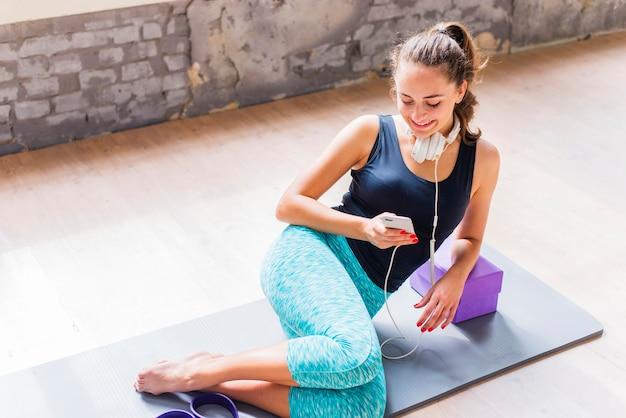 Athlétique femme assise sur un tapis d'exercice à l'aide d'un téléphone portable