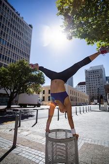 Athlétique femme effectuant le poirier et faisant une scission sur bin