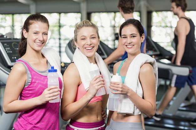 Athlétique femmes souriantes posant avec une bouteille d'eau dans une salle de sport