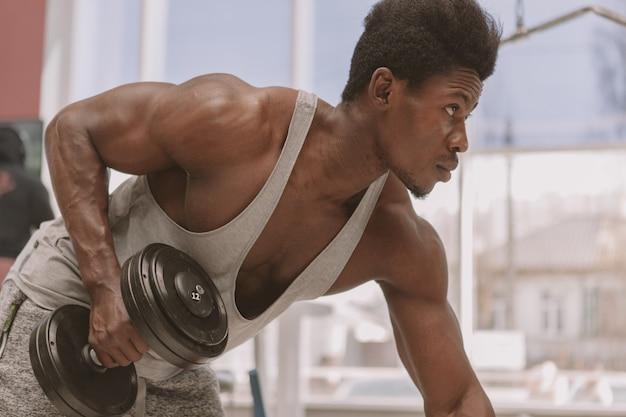 Athlétique homme africain travaillant avec des haltères à la gym