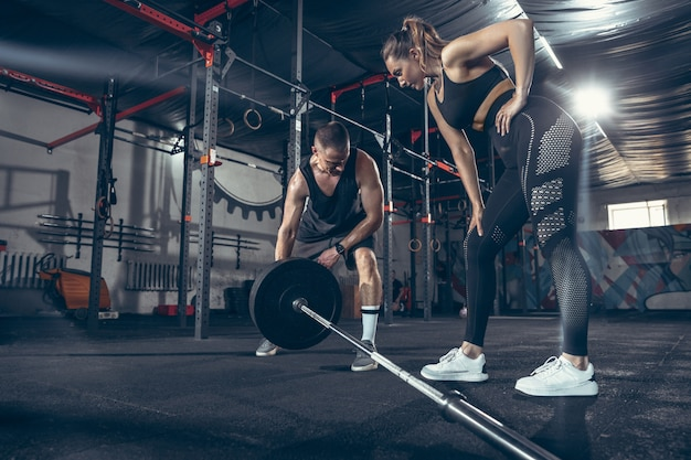 Athlétique homme et femme avec des haltères