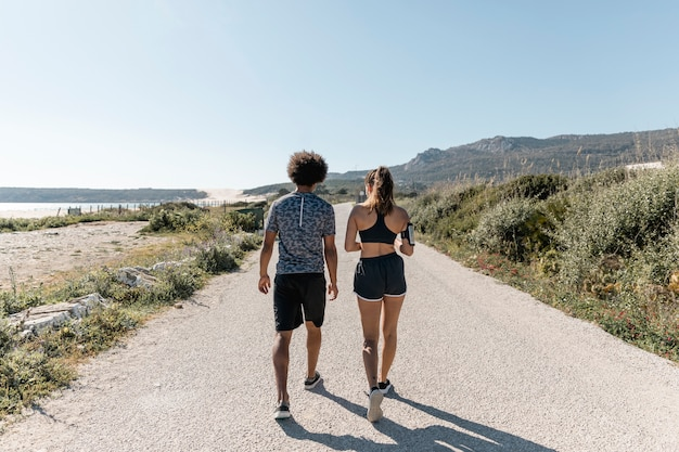 Athlétique homme et femme marchant le long de la route
