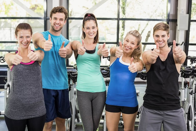 Athlétique hommes et femmes posant avec les pouces au gymnase