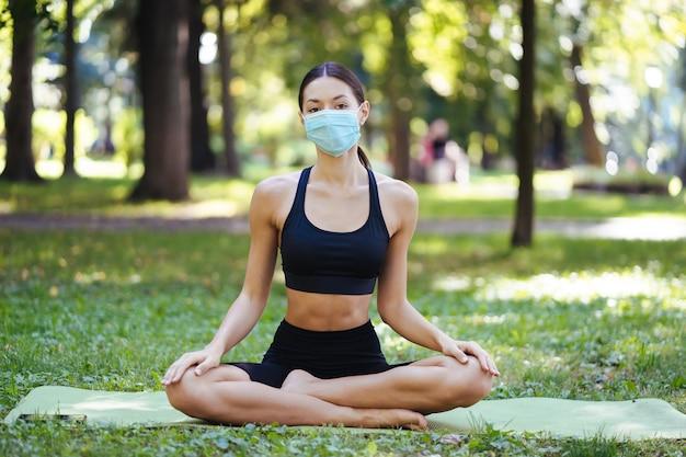 Athlétique jeune femme dans un masque de protection médicale, faire du yoga dans le parc le matin, formation des femmes sur un tapis de yoga