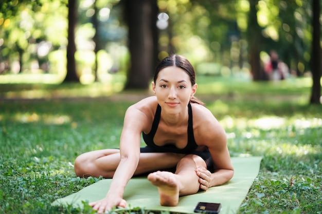 Athlétique jeune femme faisant du yoga dans le parc le matin, la formation des femmes sur un tapis de yoga