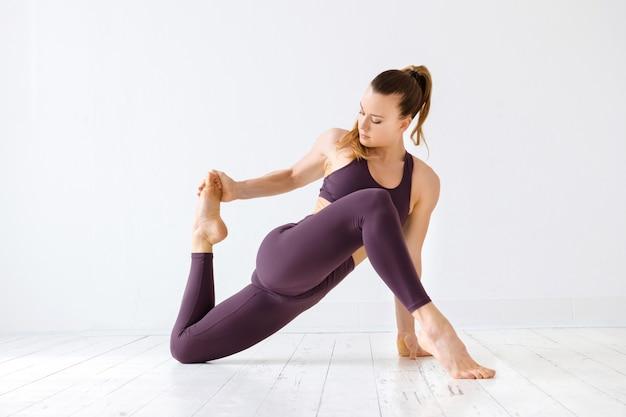 Athlétique jeune femme faisant des étirements ischio-jambiers sur ses muscles de la jambe postérieure car ils sont sujets à des blessures sportives dans une salle de sport clé dans un concept de santé et de remise en forme