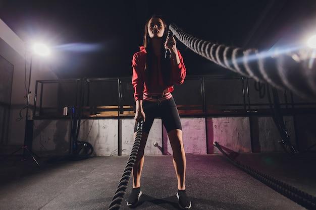 Athlétique jeune femme faisant des exercices avec une corde en plein air.
