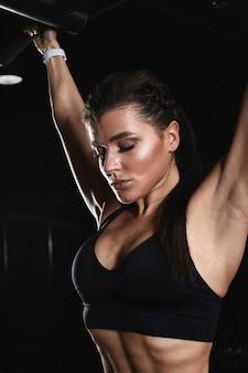 Athlétique jeune femme faisant des exercices de triceps sur un terrier dans la salle de sport