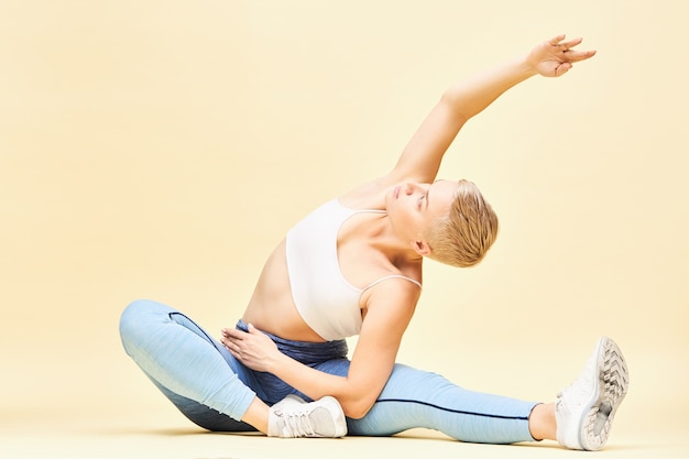 Athlétique jeune femme flexible dans des vêtements de sport élégants faisant du yoga en position assise, flexion latérale, côtes en expansion, atteignant une main. garçon fille pratiquant le pilates, assis sur le sol, qui s'étend
