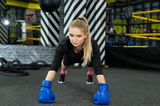 Athlétique jeune femme en gants de boxe faisant des pompes dans la salle de sport en anneau
