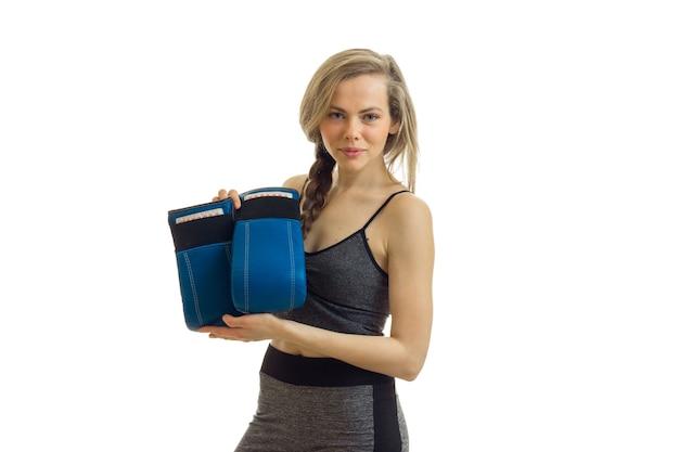 Athlétique jeune femme se penche sur l'appareil photo et détient des gants de boxe est isolé sur un mur blanc