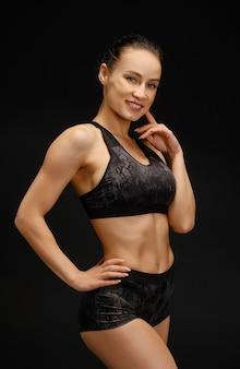 Athlétique jeune femme en vêtements de sport noir posant sur fond noir