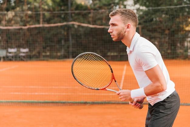 Athlétique jeune garçon jouant au tennis