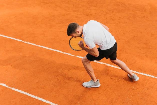 Athlétique jeune garçon remportant un match de tennis