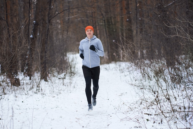 Athlétique jeune homme courir dans la forêt d'hiver et souriant