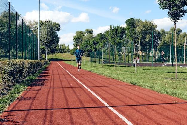 Athlétique jeune homme en cours d'exécution exercice d'étirement dans la matinée de bien-être et de sport de soins personnels
