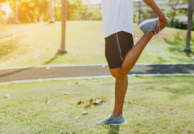 Athlétique jeune homme faisant des exercices de sport au parc public, le concept d'un mode de vie sain.