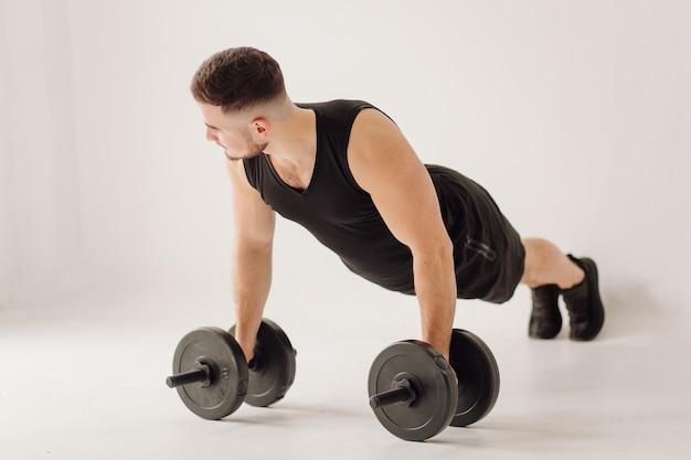 Athlétique jeune homme faisant des séances d'entraînement à la maison, homme faisant de la formation, échauffement avant l'exercice de poids.