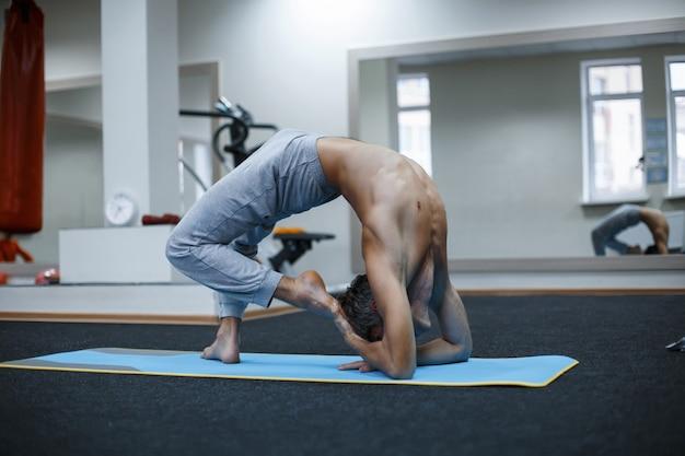 Athlétique jeune homme musclé travaillant, yoga, pilates, entraînement de remise en forme, faire un virage latéral, asana parighasana, gate yoga pose in gym