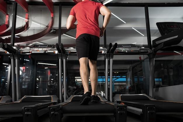 Athlétique jeune homme qui court dans la salle de gym