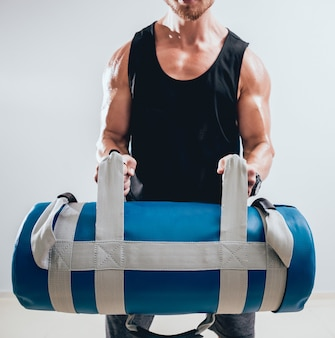 Athlétique jeune homme s'entraînant avec des sacs de sable