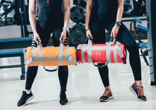 Athlétique jeunes femmes s'entraînant avec des sacs de sable sur fond gris. centre crossfit