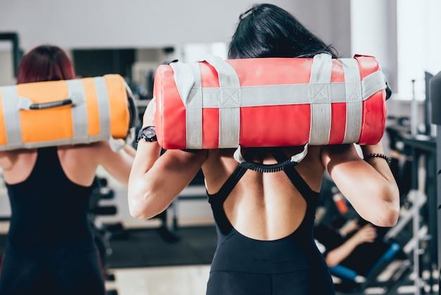 Athlétique jeunes femmes s'entraînant avec des sacs de sable