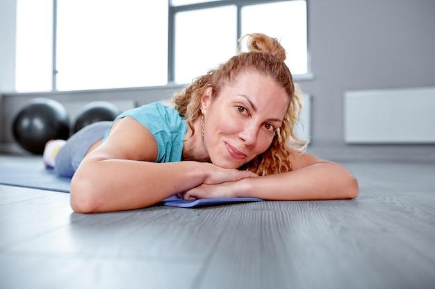 Athlétique jolie femme allongée sur un tapis de sport dans la salle de sport