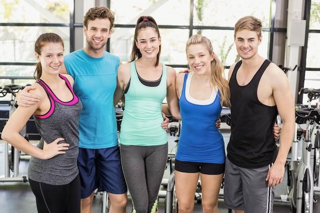 Athlétiques hommes et femmes posant ensemble au gymnase