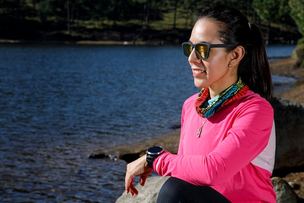 Atleta descansando en la orilla de un lago despues de correr en el bosque rodeado de arboles