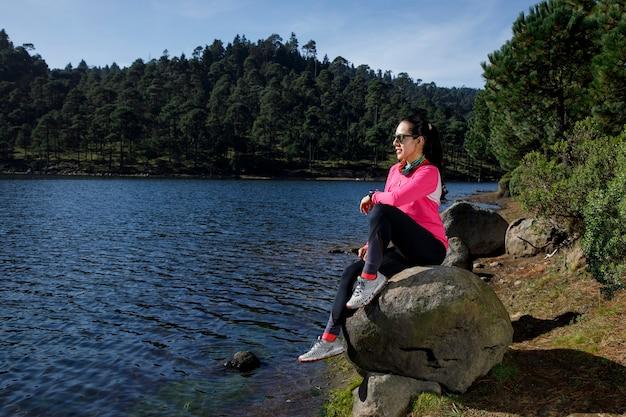 Atleta descansando a la orilla de un lago sentada sobre una piedra despus de correr en el bosque