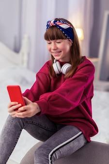 Atmosphère agréable. gentille fille gardant le sourire sur son visage tout en posant devant la caméra
