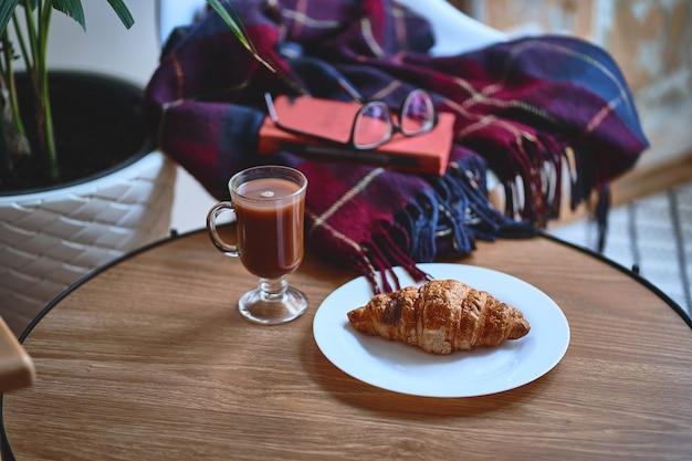 Atmosphère chaleureuse et chaleureuse. une couverture, un livre, un croissant croustillant frais sur une assiette et une tasse de chocolat chaud sur une table en bois pour un passe-temps confortable, repos et détente dans une atmosphère chaleureuse