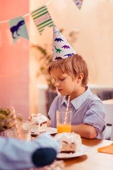 Atmosphère ennuyée. garçon concentré s'inclinant la tête tout en regardant le dessert sur la plaque