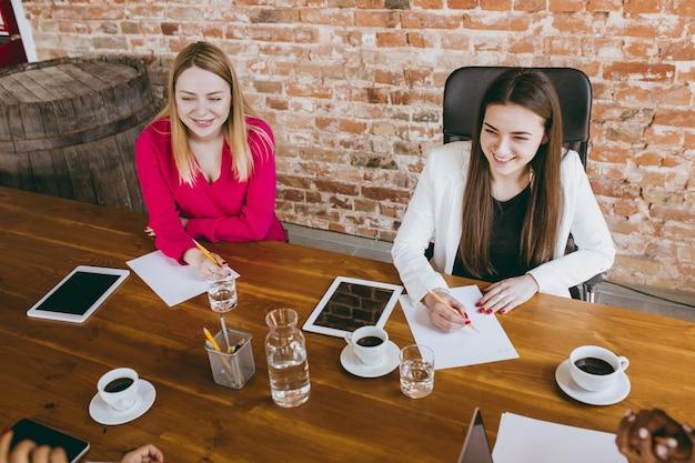 Atmosphère. jeune femme d'affaires dans un bureau moderne avec équipe. réunion créative, attribution de tâches. les femmes travaillant au front-office. concept de finance, d'affaires, de pouvoir des filles, d'inclusion, de diversité, de féminisme.