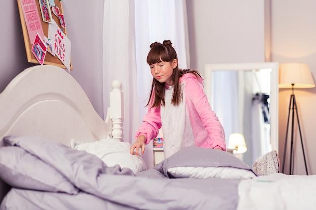 Atmosphère à la maison. écolière aimable gardant le sourire sur son visage tout en regardant des oreillers