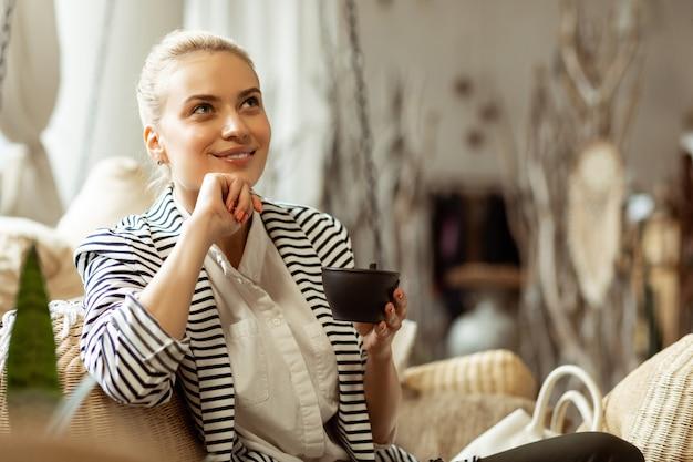 Atmosphère paisible. belle femme réfléchie avec un doux sourire tenant une tasse de thé noir tout en se relaxant dans une pièce élégante