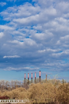 Atmosphère polluante de conduites hautes de centrale électrique au coucher du soleil.