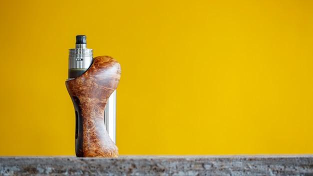 Atomiseur haut de gamme en titane genesis avec mods de boîte réglementés en bois de frêne noir naturel stabilisé dans un mur jaune, dispositif de vapotage, mise au point sélective