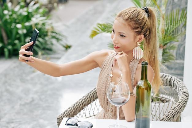 Atractive jeune femme vietnamienne assise au café en plein air avec un verre de vin et prenant selfie