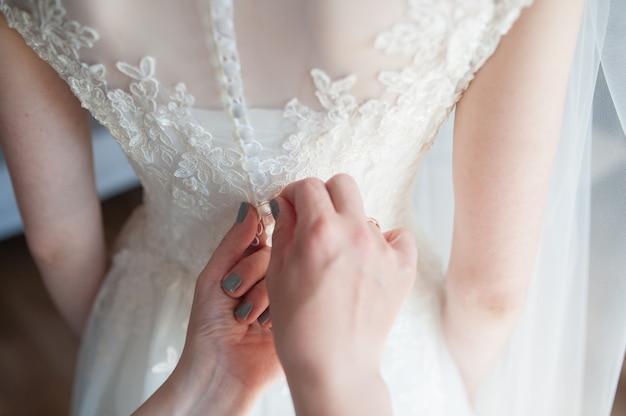 Attacher à la main le corset de la dentelle de la mariée