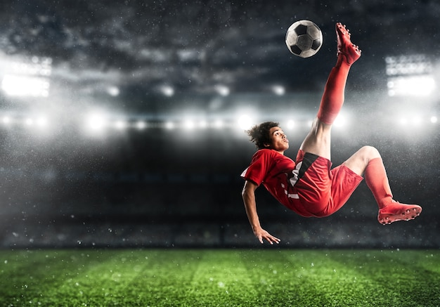 L'attaquant de football en uniforme rouge frappe le ballon avec un coup de pied acrobatique en l'air au stade