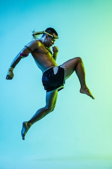 Attaque. boxer thaï de jeune homme posant sur le fond bleu dans la lumière au néon. combattant pratiquant, s'entraînant aux arts martiaux en action. santé, sport, concept de culture asiatique. copiez l'espace pour l'annonce. muay thaï.