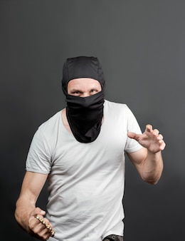 Une attaque de délinquant avec des poings américains. coup de poing américain en métal dans la main d'un homme de race blanche au masque noir. armes interdites dans un combat, criminel. homme américain montrant le poing avec des poings américains. fermer
